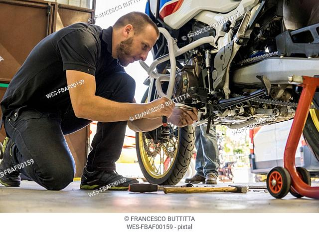 Mechanic working on motorcycle in workshop