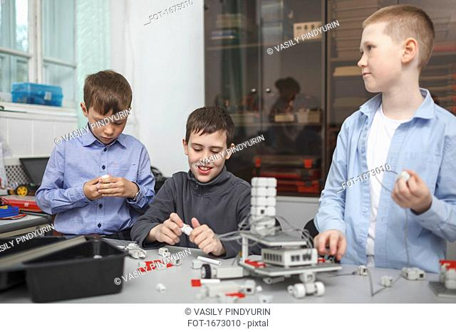 Smiling students working on machine part at table in classroom
