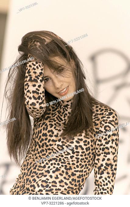 portrait of woman ruffling hair, wearing fashionable leopard print sweater, in Munich, Germany