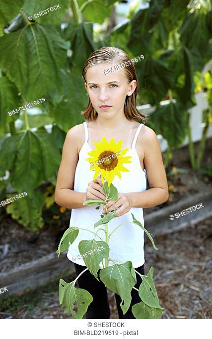 Close up of girl holding sunflower in garden