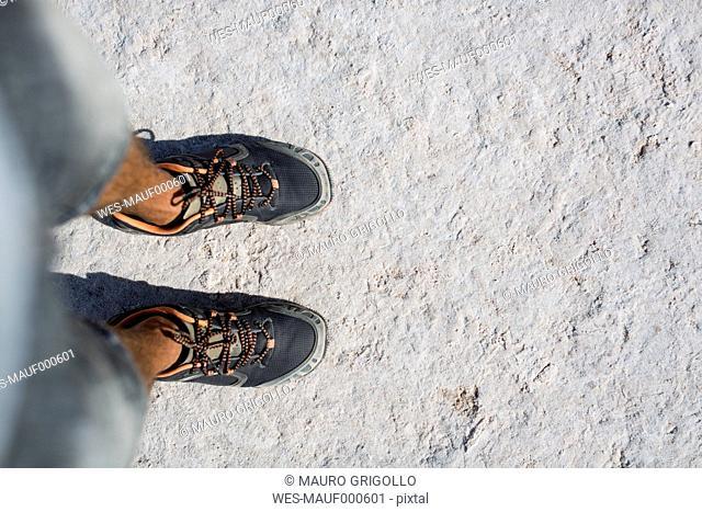 Chile, San Pedro de Atacama, man's feet in the desert