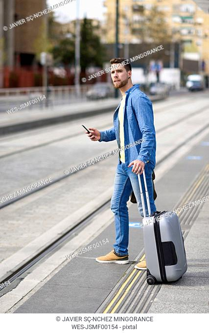 Young man waiting at a station with smartphone in his hand and trolley