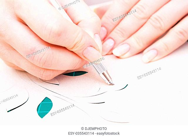 woman's hand cutting flower from paper with paper-knife