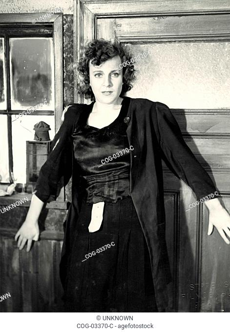 An actress wearing a black dress in a scene from a movie