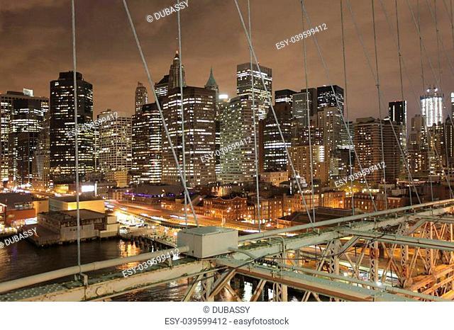 shot of lower manhattan from brooklyn bridge at night