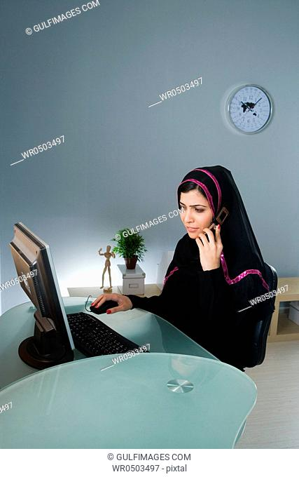 Arab woman using cellphone in front of computer