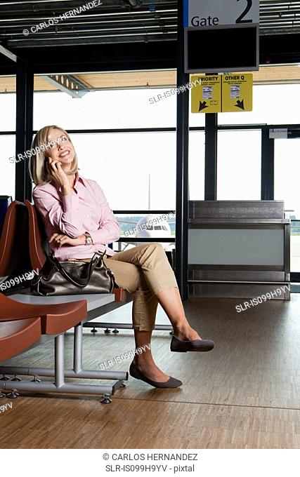 Mid adult woman on the phone in airport departure lounge