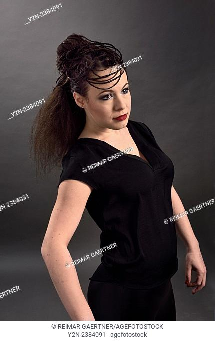 Model in black impersonating mannequin with hair style