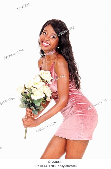 A beautiful young African woman standing in a short pink dress holding a bunch of yellow roses, isolated for white background