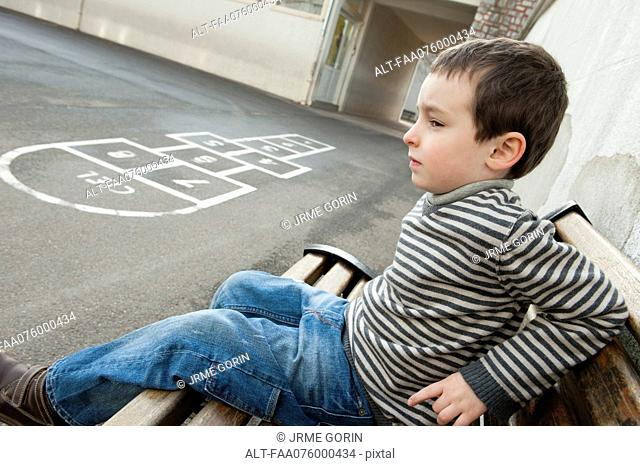 Boy sitting on bench, looking sad