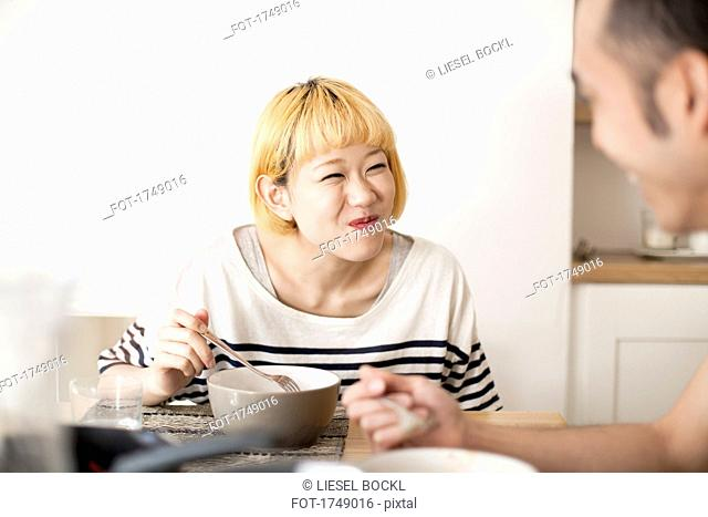 Happy young woman making face while having breakfast with man in house
