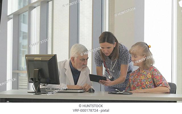 Doctor with Muscular Dystrophy studying patient data with two nurses