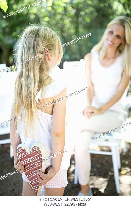 Daughter hiding heart behind her back looking at mother
