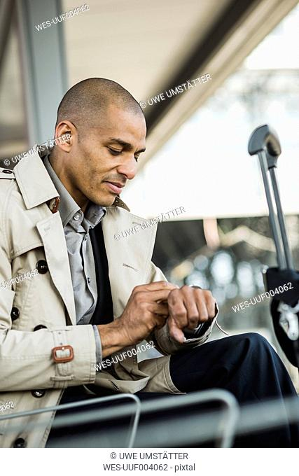 Businessman outdoors checking the time