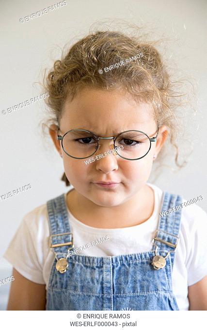 Portrait of angry little girl wearing glasses