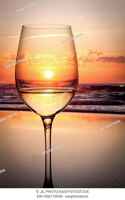 Backlit glass of water reflecting sunset