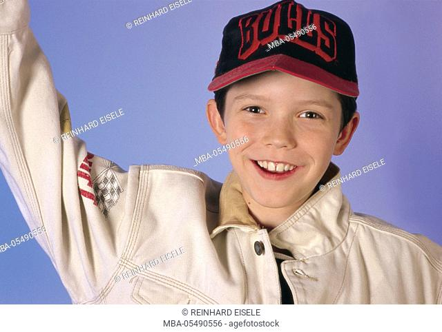 Boy rejoices, is pleased, laughs, pulls an arm upwards