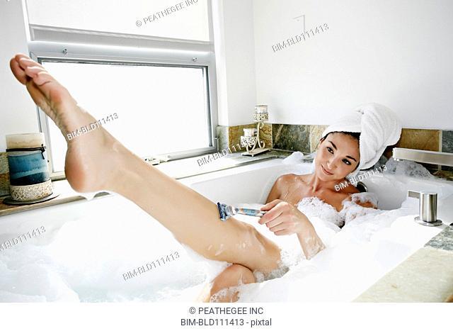 Mixed race woman shaving in bubble bath