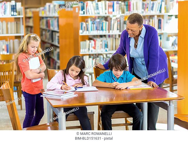 Teacher helping students in library