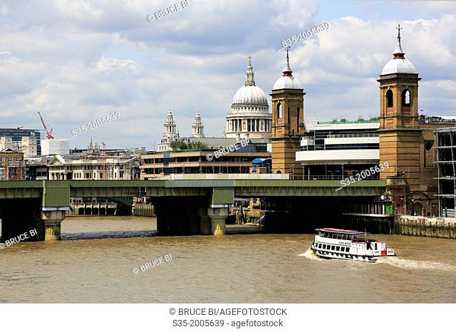 A tour boat River in Thames with Cannon Street Railway Bridge and the dome of St Paul's Cathedral in the background. London. England. United Kingdom