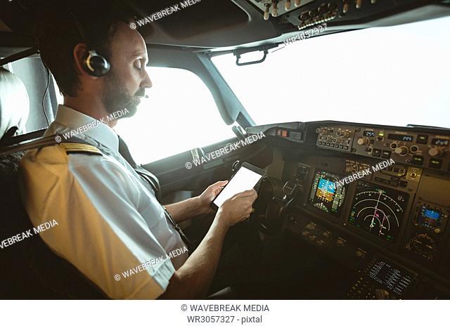 Pilot using digital tablet in airplane