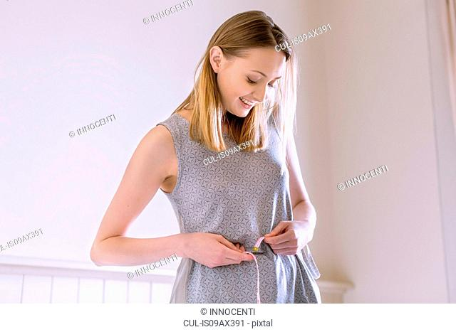 Woman measuring waist with tape measure looking down smiling