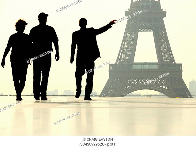 Silhouette of people walking in front of the Eiffel Tower