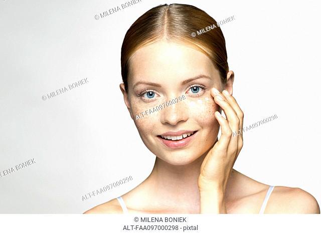 Young woman applying undereye cream