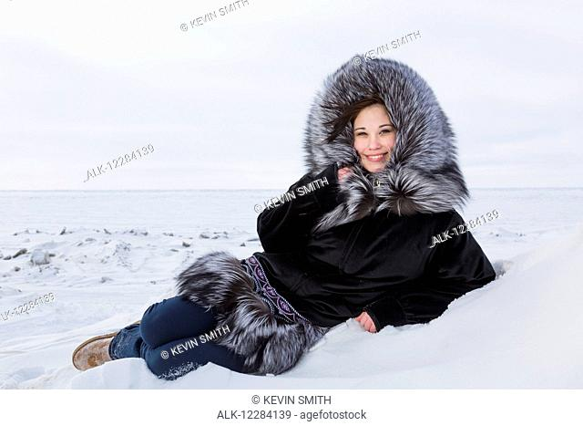 Female native youth wearing a traditional fur parka while lying on ice along the Arctic Ocean, Barrow, North Slope, Arctic Alaska, USA, Winter