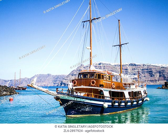 Gorgeous small sailboat that cruises on the Cyclades island to go visit the volcano, in Santorini, Greece. The water is clear, blue and green