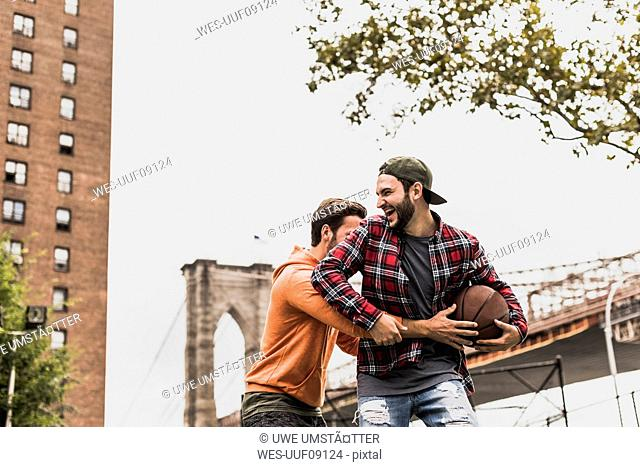 USA, New York, two young men with basketball having fun on an outdoor court