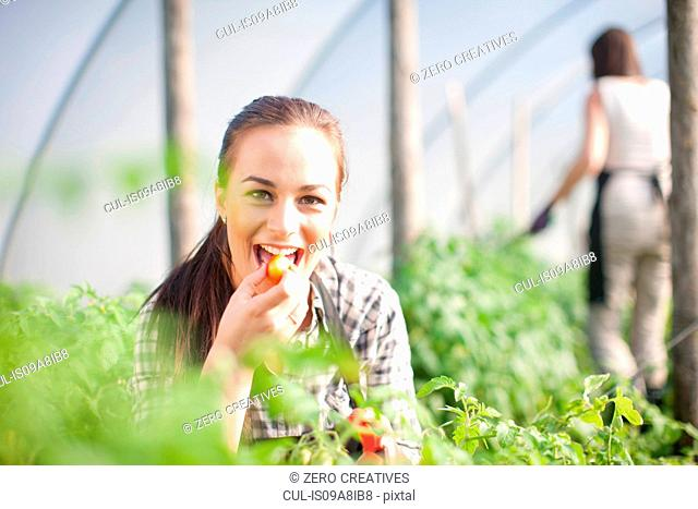 Young woman trying produce at vegetable farm