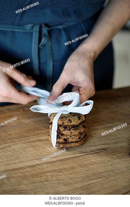Woman's hands packing home-baked vegan chickpea cookies, partial view