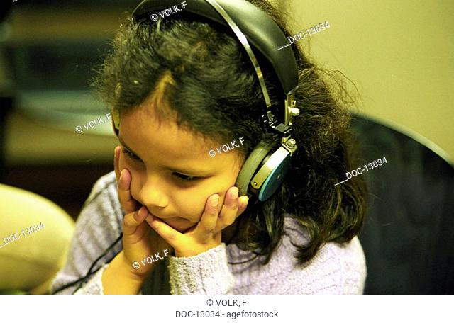 Portrait - Pre-teen girl subjects herself to a listening test