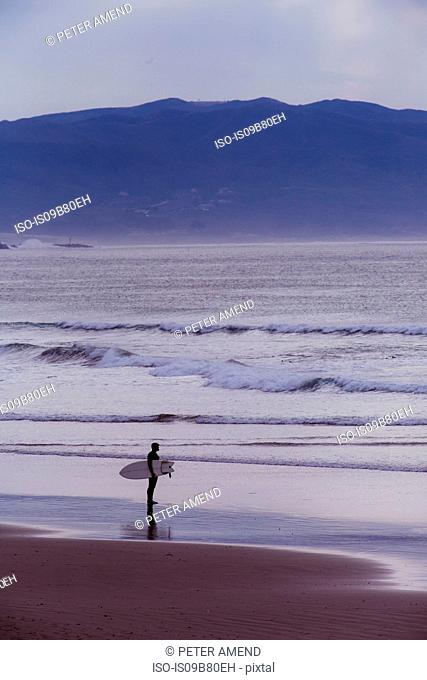 Young male surfer looking out over sea, Morro Bay, California, USA