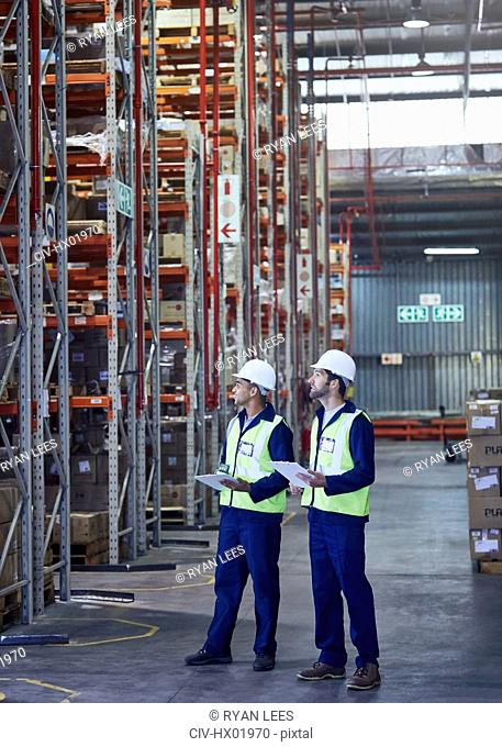 Workers with clipboards looking away in distribution warehouse