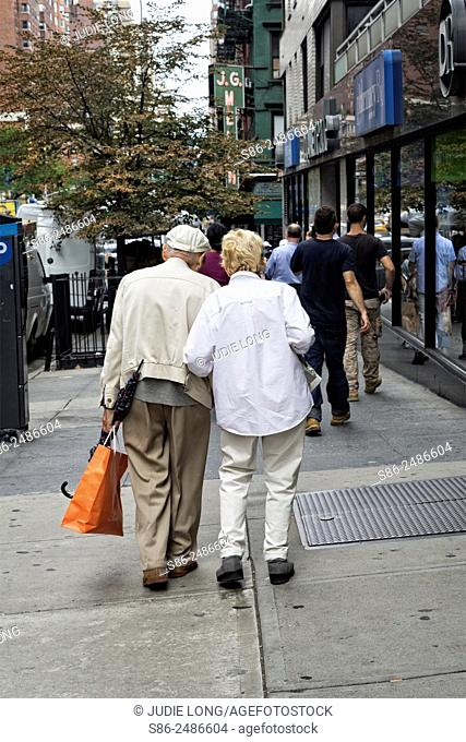 Very Elderly Unidentifiable, Man and Woman Couple, Walking along a Manhattan, New York City Street