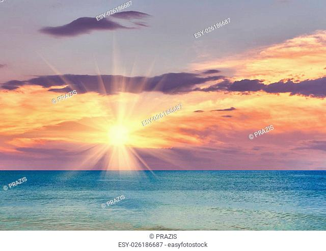 Beautiful sea sunset cloudy sky piercing rays of the sun