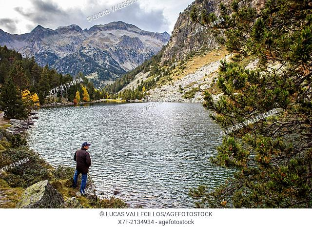 Hiker.`Estany Llong',Llong lake,Aigüestortes i Estany de Sant Maurici National Park,Pyrenees, Lleida province, Catalonia, Spain