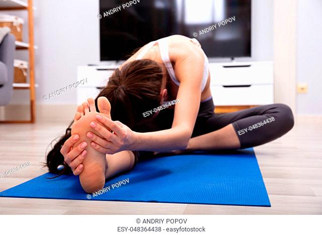 Fit Woman Stretching Her Leg On Blue Exercise Mat At Home