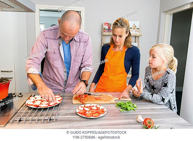 Kaatsheuvel, Netherlands. Mid adult man and woman preparing tomatoes for a sidedish with Lasagna dis diner, observed by their young daughter