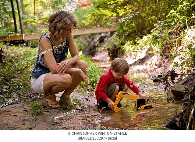 Caucasian mother watching son playing with construction toys in river