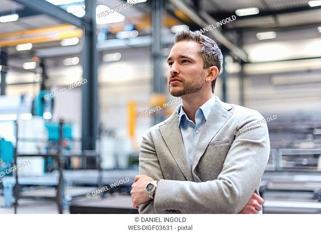 Portrait of businessman on factory shop floor thinking