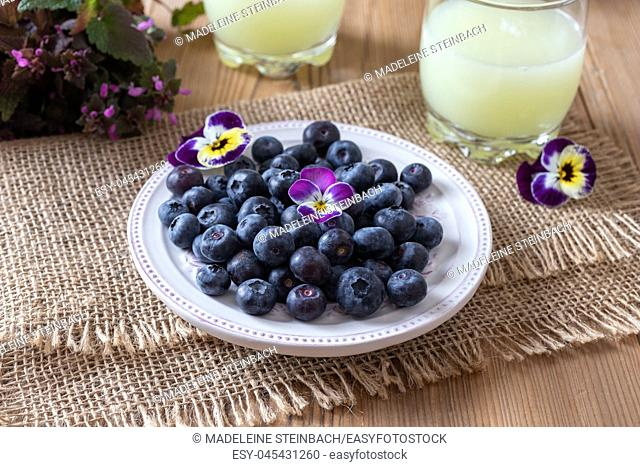 Blueberries on a plate, with fresh whey in the background