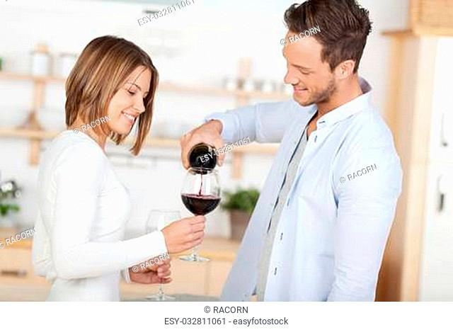 Handsome man gives his wife a red wine at home