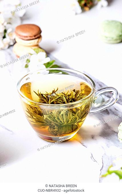 Glass cup of hot green tea with french dessert macaroons, spring flowers white magnolia and cherry blooming branches over white marble texture background