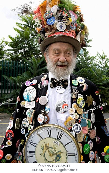 Bearded old man in carnival costume. Lots of badges & top hat. Notting Hill Carnival. Notting Hill. London. England. UK