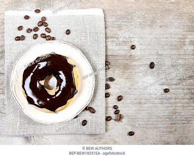 Delicious donut with chocolate on wooden table. Top view, copy space