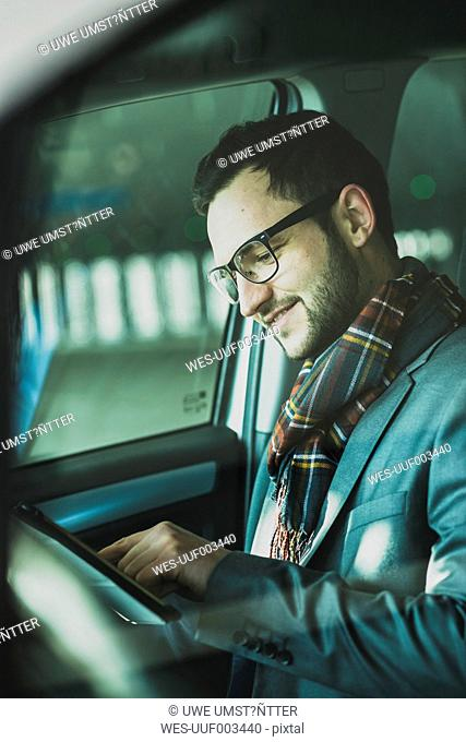 Young businessman in car looking at digital tablet