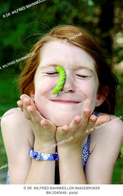 Girl with a huge caterpillar on her face